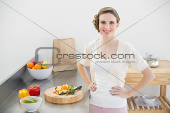 Attractive woman posing in her kitchen with hands on hips