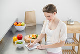 Happy beautiful woman standing in her kitchen writing on a notebook