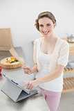 Content woman working with her tablet standing in the kitchen