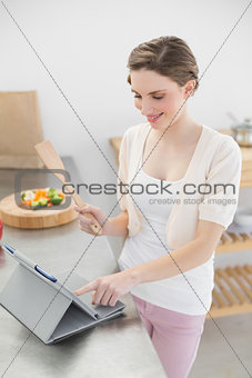 Smiling brunette woman using her tablet while standing in her kitchen