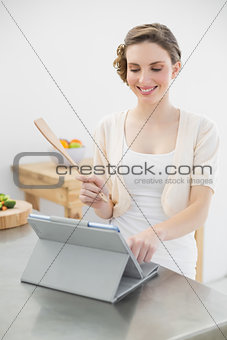 Smiling brunette woman standing in her kitchen while working with her tablet