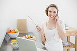 Smiling beautiful woman phoning while standing in the kitchen in front of her laptop