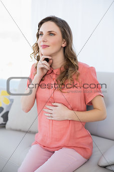 Thoughtful pregnant woman sitting on a couch in the living room