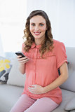Content calm pregnant woman holding her smartphone sitting on couch