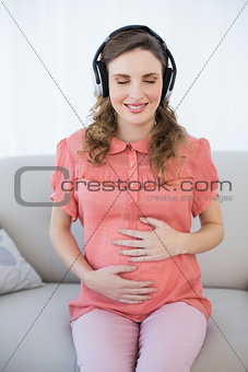 Pregnant woman relaxing sitting on couch with closed eyes