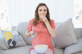 Cute pregnant woman eating popcorn while watching television