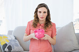 Cute pregnant woman holding a piggy bank while sitting on couch