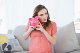 Lovely pregnant woman shaking a piggy bank sitting on couch