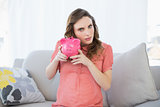 Beautiful pregnant woman shaking a piggy bank sitting on couch