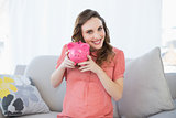 Smiling pregnant woman shaking pink piggy bank sitting on couch