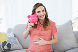 Content pregnant woman shaking pink piggy bank sitting on couch