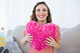 Cheerful pregnant woman holding pink heart pillow sitting on couch