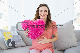 Content pregnant woman holding a pillow sitting on couch in living room