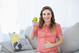Young pregnant woman showing green apple sitting on couch in living room