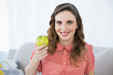 Smiling pregnant woman presenting green apple sitting in living room