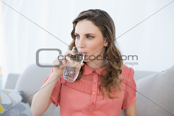Beautiful pregnant woman drinking glass of water sitting on couch in living room