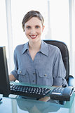 Cute young businesswoman sitting at desk in office