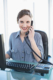 Casual pretty businesswoman phoning with telephone at desk