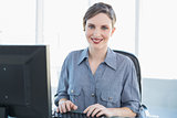 Content businesswoman working on computer at her desk