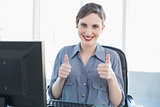 Cheerful businesswoman showing thumbs up sitting at he desk