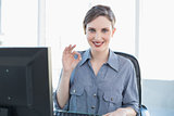 Lovely young businesswoman making a gesture sitting at her desk