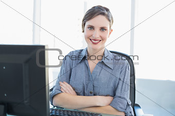 Cute young businesswoman sitting at her desk with arms crossed