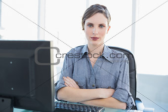 Attractive female businesswoman sitting at her desk with arms crossed