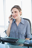 Cute businesswoman phoning with her smartphone sitting at her desk