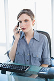 Serious young businesswoman phoning with her smartphone sitting at her desk