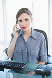 Serious female businesswoman sitting at her desk while phoning with her smartphone