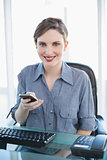 Smiling businesswoman holding her smartphone in the office