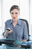 Businesswoman holding her smartphone sitting at her desk