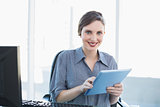 Portrait of attractive young businesswoman using her tablet sitting at her desk