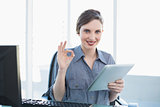 Attractive calm businesswoman showing thumbs up while holding her tablet