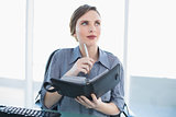 Thinking businesswoman holding her diary while sitting at her desk
