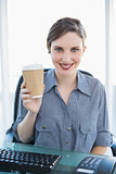Cheerful young businesswoman presenting disposable cup