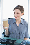 Cute businesswoman looking at disposable cup sitting at her desk