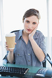 Tired casual businesswoman holding a disposable cup while sitting at her desk