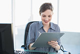 Content attractive businesswoman writing on clipboard sitting at her desk