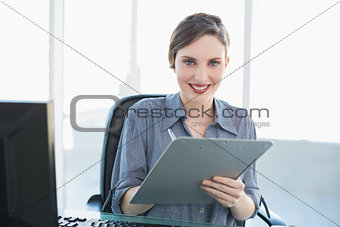Portrait of beautiful businesswoman holding a clipboard sitting at her desk