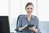 Smiling peaceful businesswoman using a calculator sitting at her desk