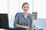 Joyful young businesswoman showing calculator sitting at her desk