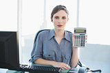 Calm businesswoman showing calculator sitting at her desk