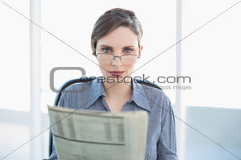 Focused businesswoman holding newspaper sitting at her desk