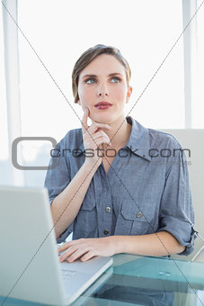Thoughtful businesswoman using her notebook while sitting at her desk