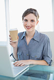 Content businesswoman showing disposable cup sitting at her desk