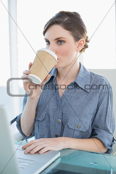 Beautiful businesswoman drinking of disposable cup sitting at her desk
