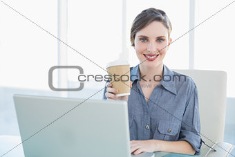 Calm beautiful businesswoman showing disposable cup while sitting at her desk