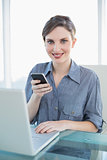 Portrait of pretty calm businesswoman holding her smartphone sitting at her desk