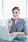 Beautiful smiling businesswoman holding a glass of water sitting at her desk